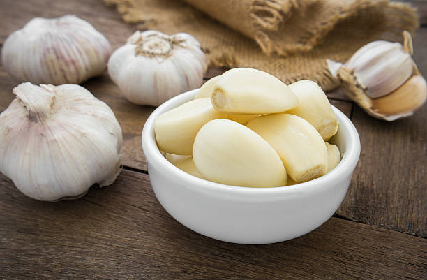 Peeled garlic in bowl stock photo