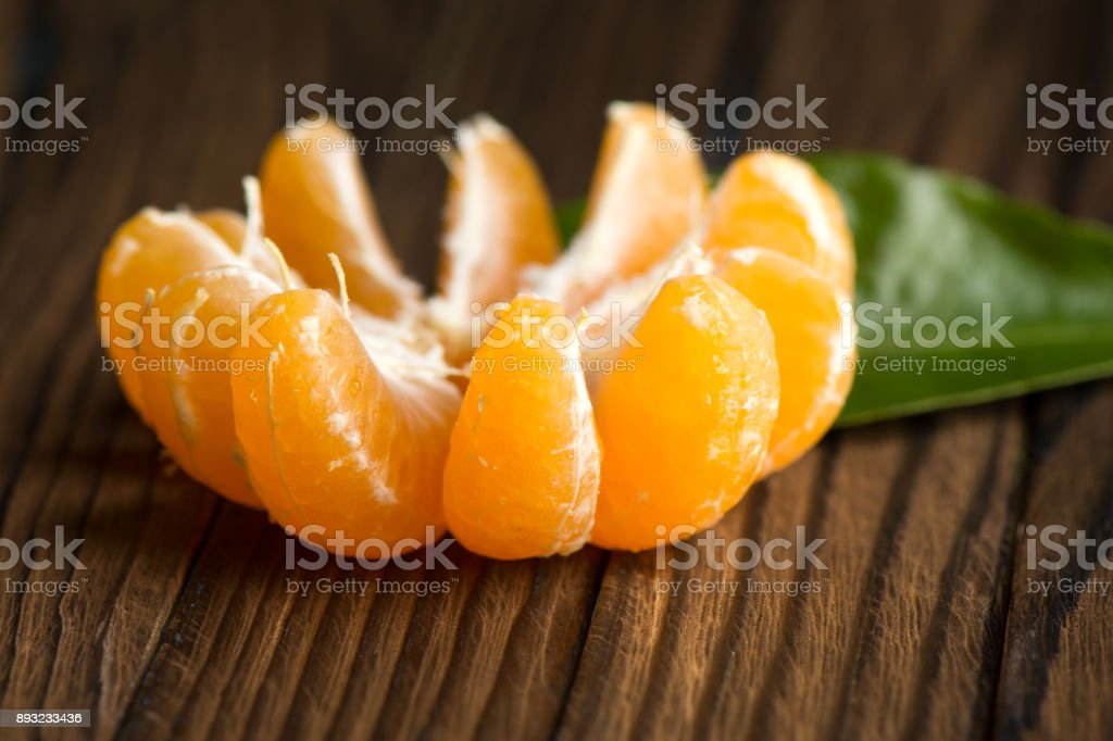 Peeled Mandarin slices on a wooden table stock photo