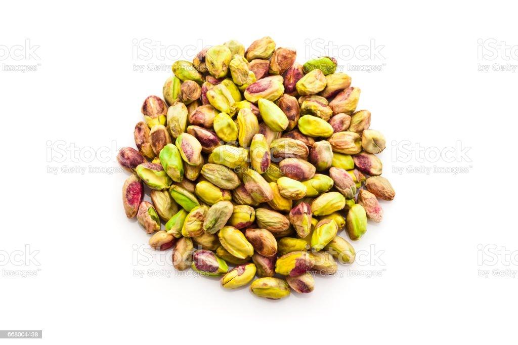 Peeled pistachio nuts heap isolated on white background stock photo