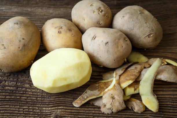 Geschälte Kartoffeln und Haufen von Kartoffeln auf rustikalen Holztisch – Foto