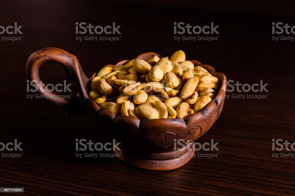 Peeled roasted peanuts in ceramic bowl on wooden table stock photo