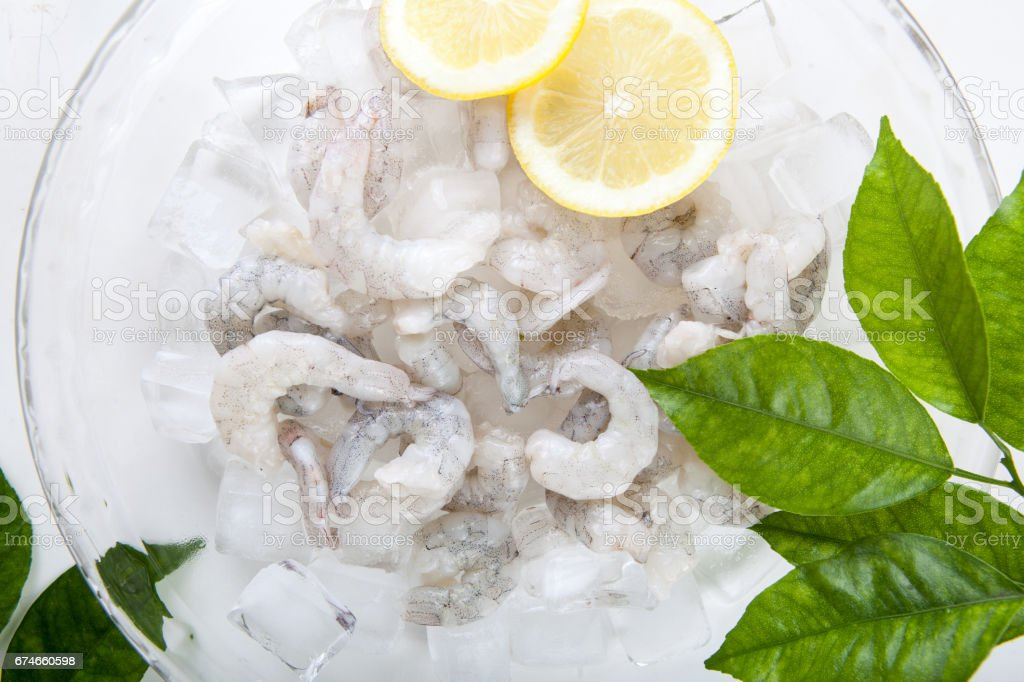 Peeled Shrimp on ice cube with fresh lemon and green leaf stock photo