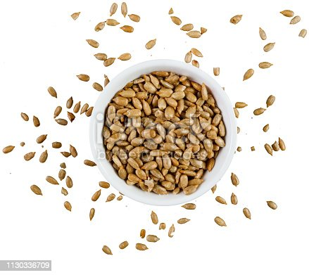 Heap of peeled and roasted sunflower seeds in a bowl on white background shot directly from above