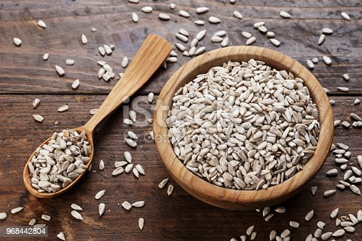 Peeled sunflower seeds on a wooden background in a plate. place for text