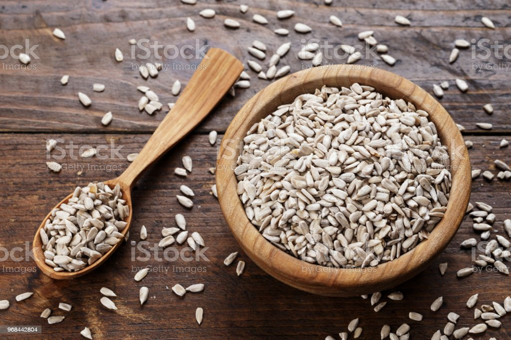 Peeled sunflower seeds on a wooden background in a plate. stock photo