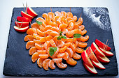 Peeled tangerine slices and apple skewers, served on black stone tray