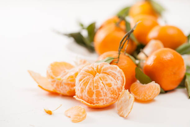 Peeled tangerines and peel with leaves on white background Fresh tangerines with leaves and peeled tangerines, sliced with peel. The beneficial properties of mandarins for health. tangerine stock pictures, royalty-free photos & images