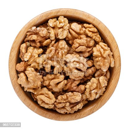Peeled walnuts in wooden bowl isolated on white. Top view.