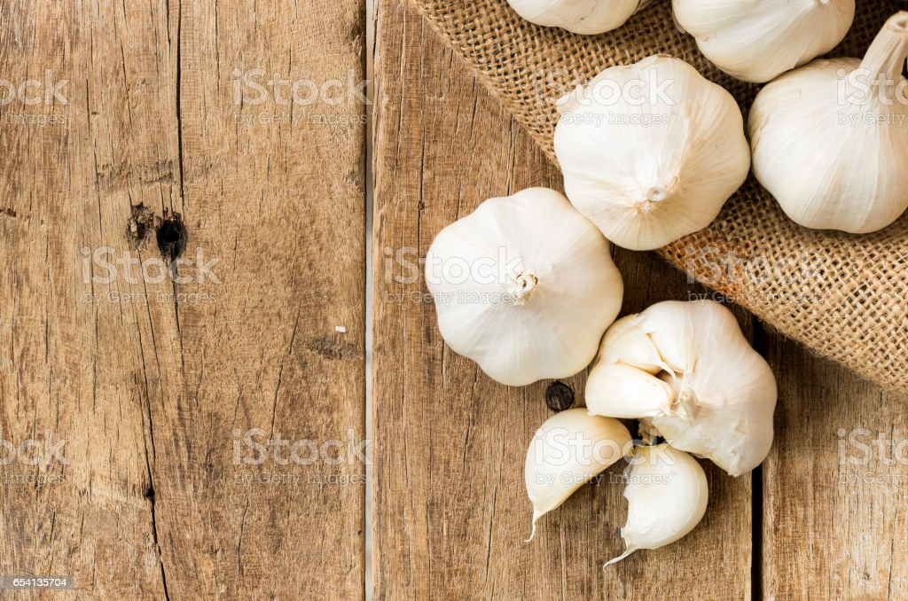 peeled white garlic in gunny sack cloth on brown wooden table - fotografia de stock