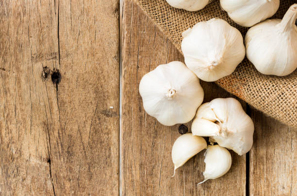 peeled white garlic in gunny sack cloth on brown wooden table stock photo