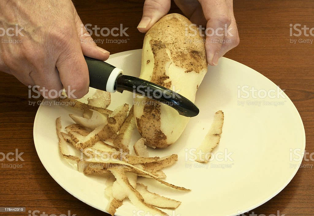 peeling a potato royalty-free stock photo