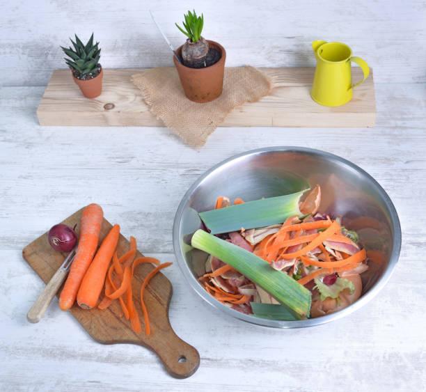 pelar zanahorias en un tablón de cocina y un tazón lleno de residuos en una mesa en una cocina - foto de stock
