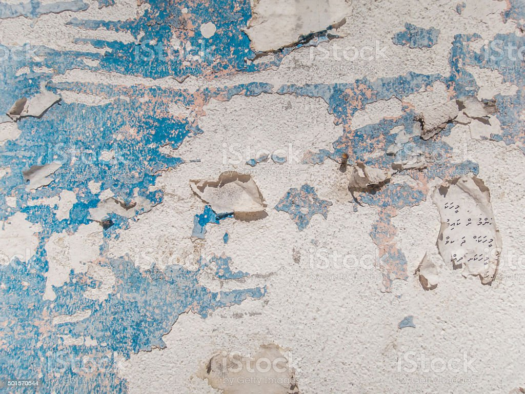 Peeling paint and paper on cement wall stock photo