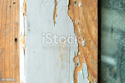 Peeling paint from wooden surface as part of old wooden doors.