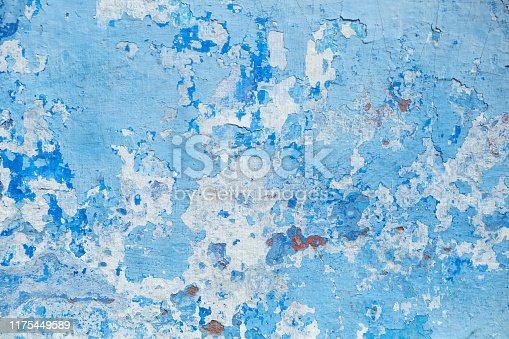 Macrophotography of a damaged wall with a peeled paint and cracked wall