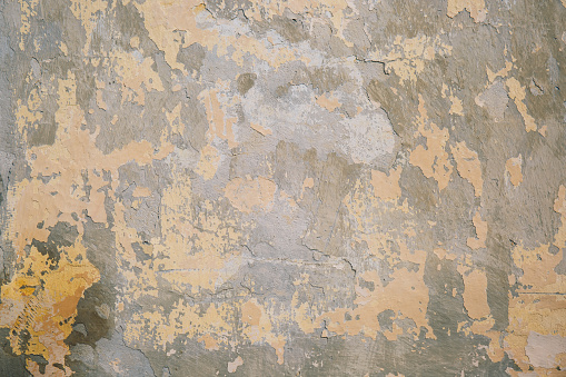 Peeling paint on concrete wall close up. Texture background.