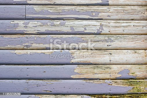 Peeling purplish blue paint on the old wooden planks of the facade of a house in Iceland
