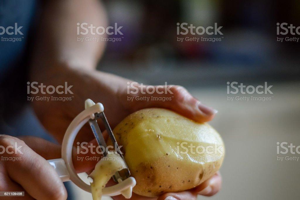 Peeling Potatoes - close up stock photo