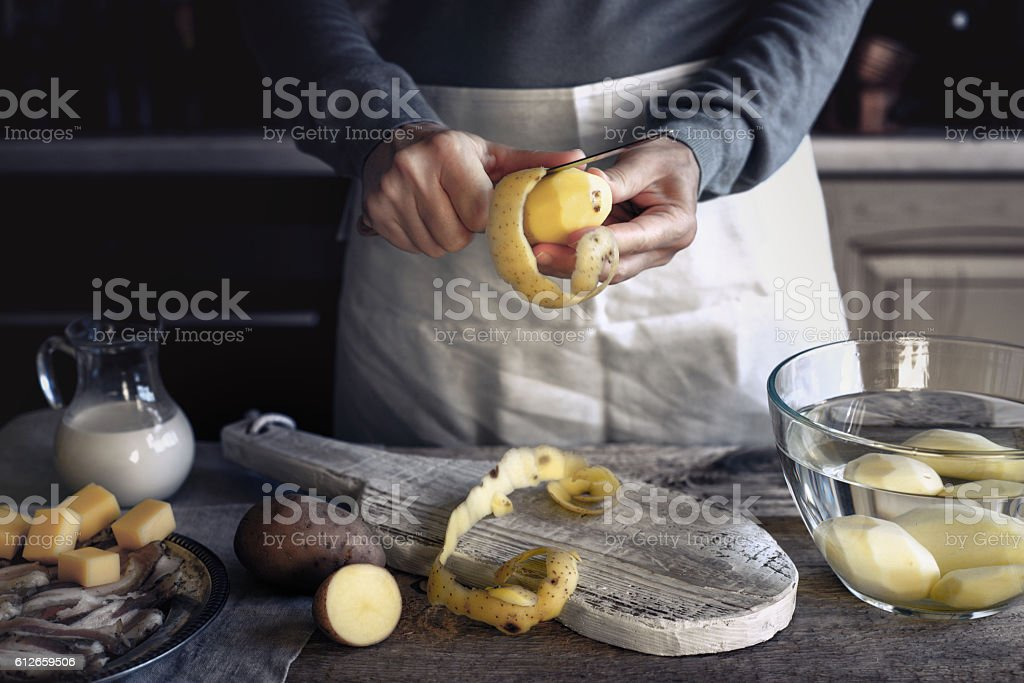 Peeling potatoes on the wooden table horizontal stock photo