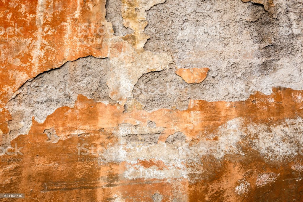 Peeling rusty paint on stone wall. Old worn and aged exterior. royalty-free stock photo