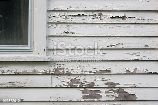 Peeling white paint on a calpboard hose with part of window