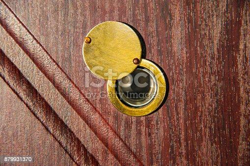 istock Peephole on wooden door - judas hole spyhole 879931370