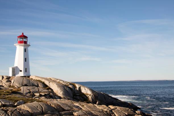 Peggys Cove Lighthouse, Nova Scotia, Canada along rocky shores stock photo