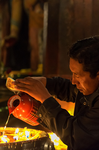 Local Tibetan lighting Butter lamp in monastery and donating money in the temple. Tibet, China.