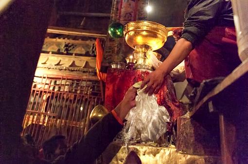Local Tibetan donating hadas and money in monastery. Tibet, China.