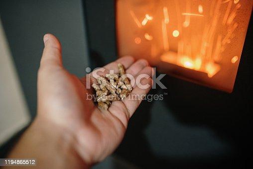 Pellet / Biomass heating - Human hand holding biomass pellets by a fireplace