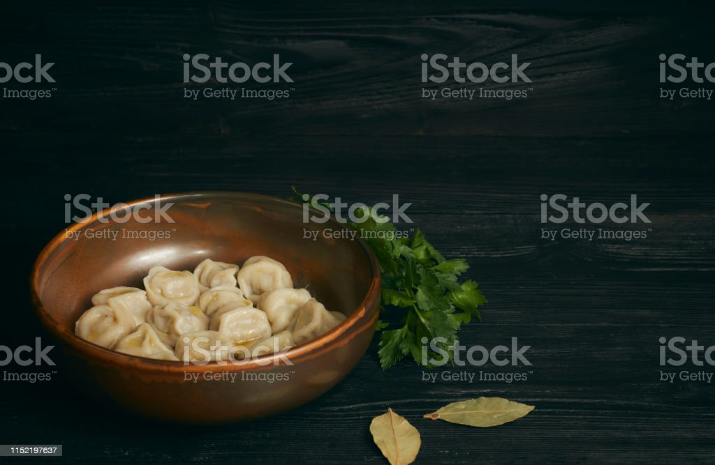 pelmeni with butter and greens on a black wooden table. Russian...
