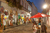 Salvador, Bahia, Brazil - October 3, 2012: Two women and a boy sell candies in front of a souvenir shop in Pelourinho district, late afternoon.