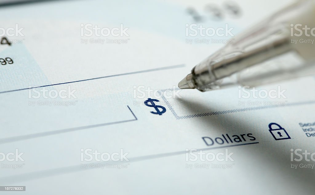 A pen about to almost hit the paper check to enter an amount stock photo