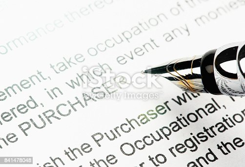 A fountain pen hovers over a legal sales document.