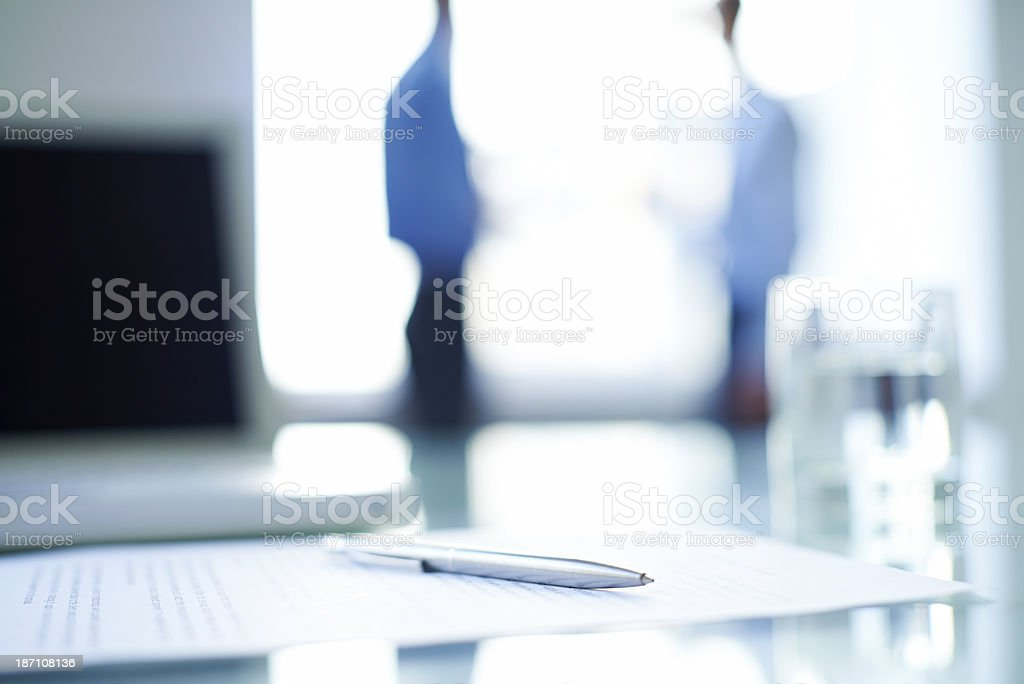 Pen across a business contract on office desk stock photo