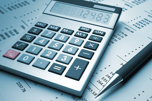 A pen and a calculator sit on a page with numbers stock photo