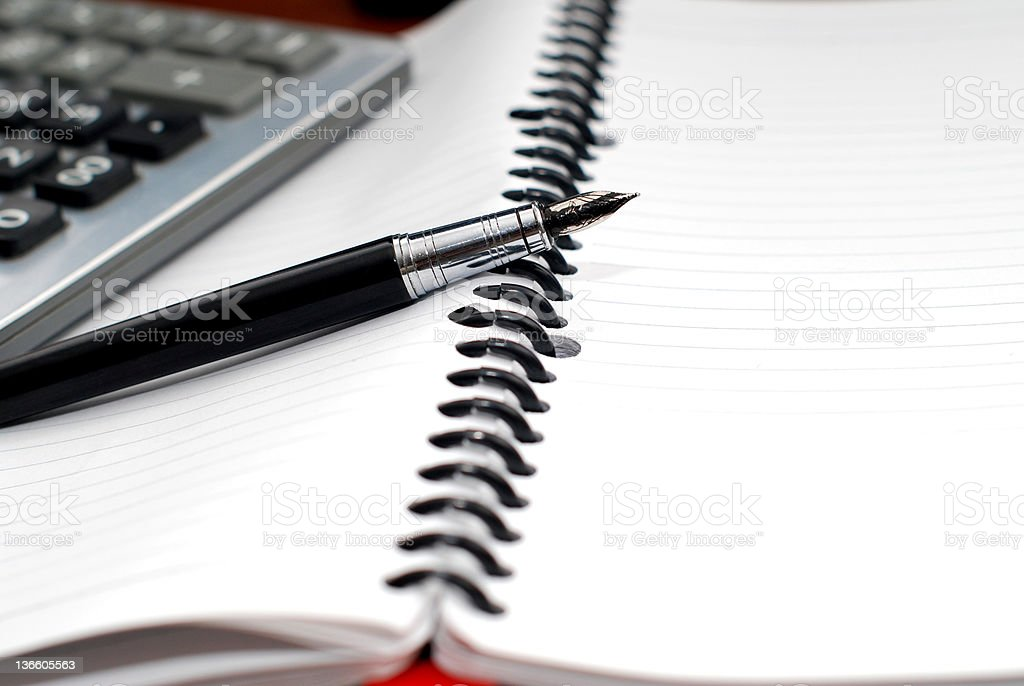 Pen and calculator on notebook stock photo