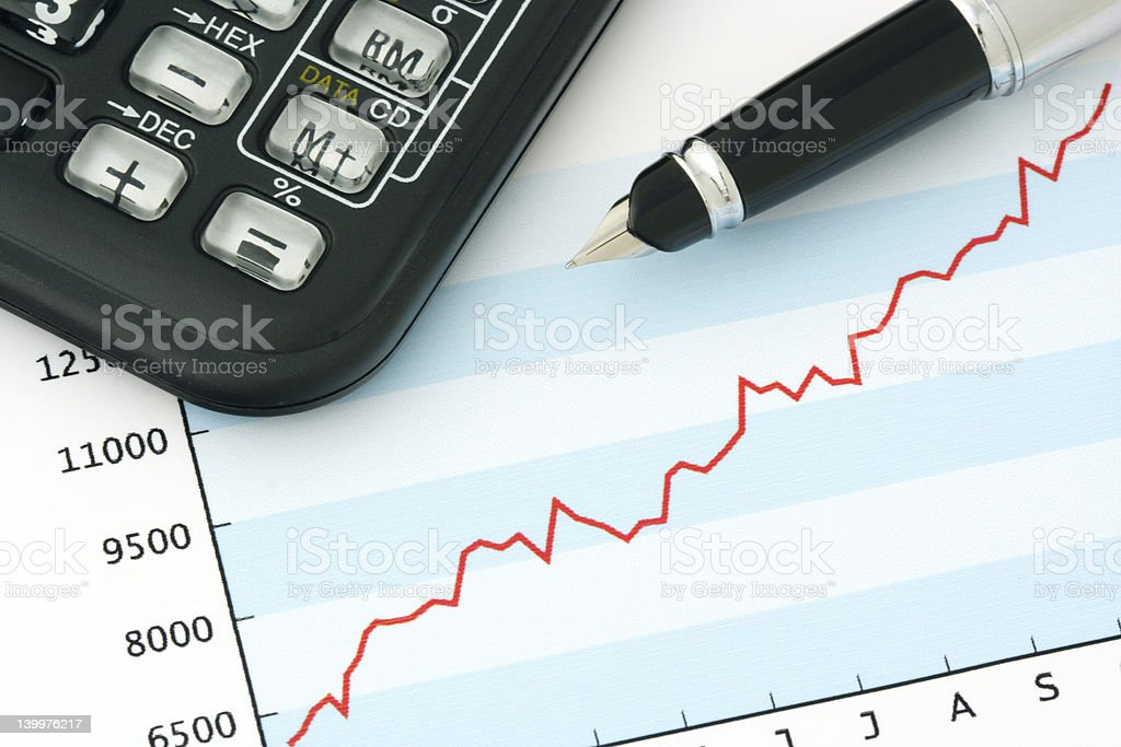 Pen and Calculator on Positive Earning Graph royalty-free stock photo