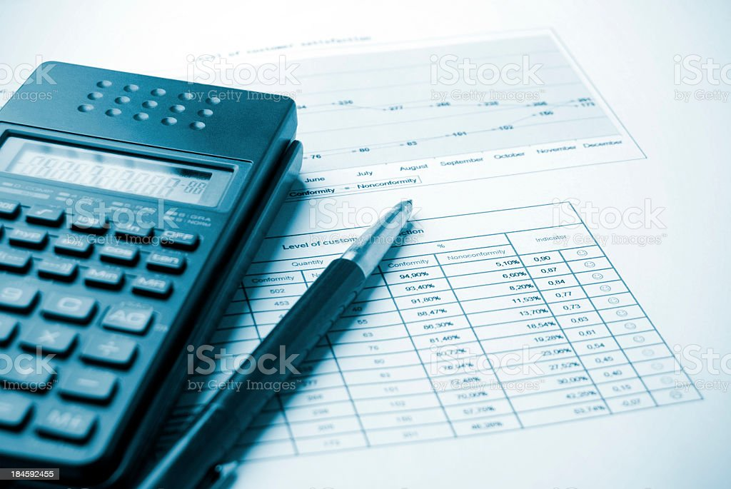 Pen and calculator resting on budget charts Budget analysis background Analyzing Stock Photo