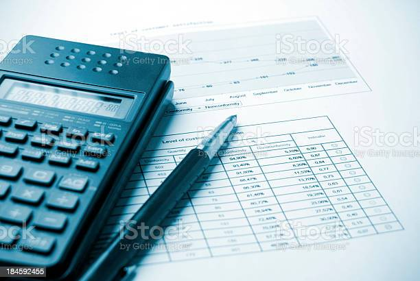 Pen And Calculator Resting On Budget Charts Stock Photo - Download Image Now