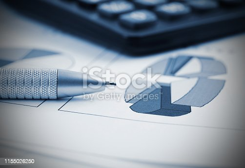 851244800istockphoto Pen and Calculator resting on Business Charts 1155026250