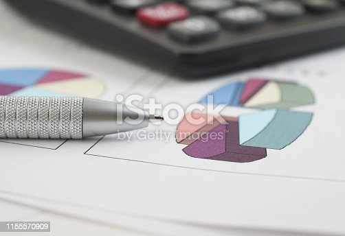 istock Pen and Calculator resting on Business Charts 1155570909