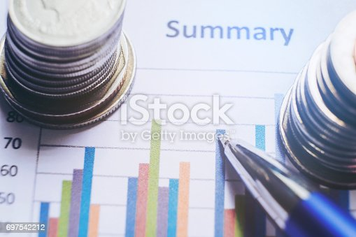864278180istockphoto Pen and coin on the business paper. Report chart 697542212