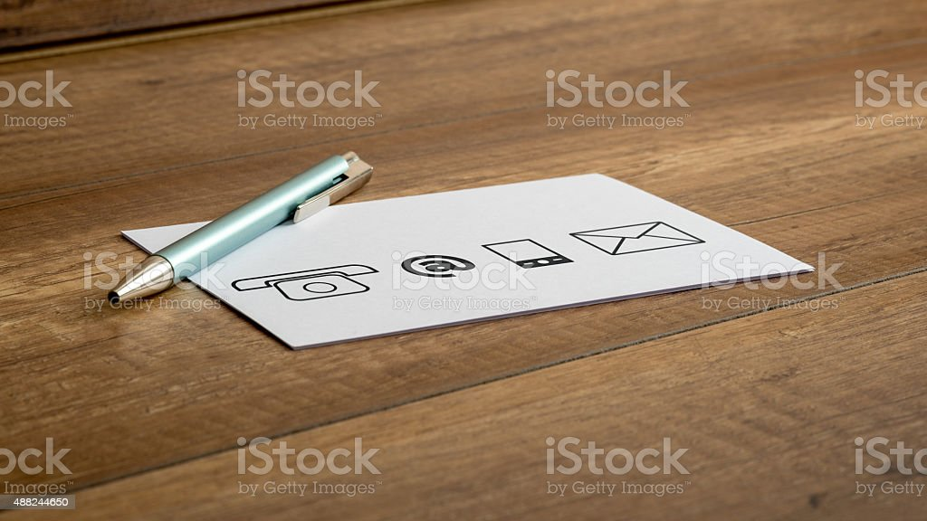 Pen and contact icons printed on a white card stock photo