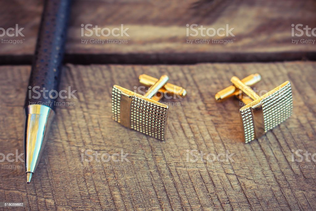 Pen and cufflinks on the old wood background. Toned image. stock photo