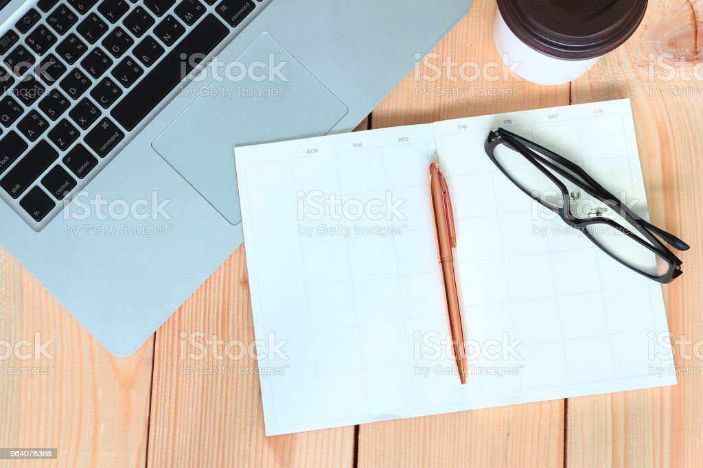 Pen and glasses lay on blank diary book and labtop and coffee cup on wood table,business concept. - Royalty-free Backgrounds Stock Photo