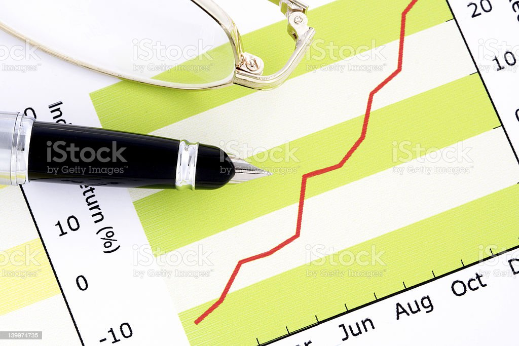 Pen and Glasses on Positive Earning Graph royalty-free stock photo