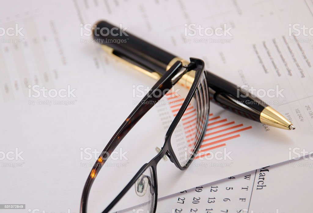 pen and glasses on stock chart stock photo