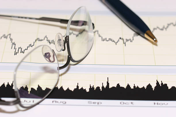 Pen and glasses over graphic paperwork stock photo