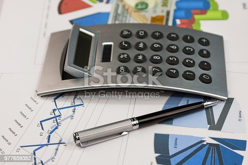 istock Pen, calculator and dollars are on the charts. 977659352